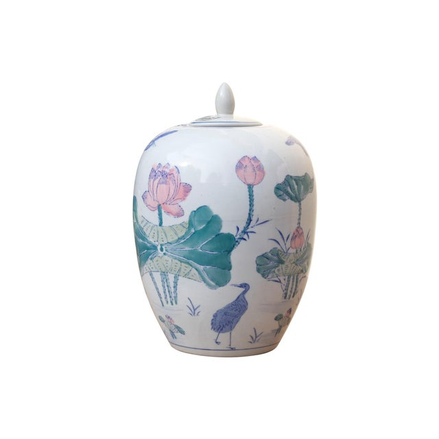 A Chinoiserie ceramic ginger jar with inset lid. Decorated with hand painted lotus flowers with furled leaves and Jacana...