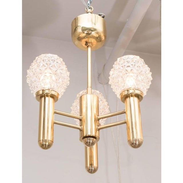 A chic Mid-Century Modernist three-arm brass chandelier with relief glass globes. A polished brass frame with rounded...