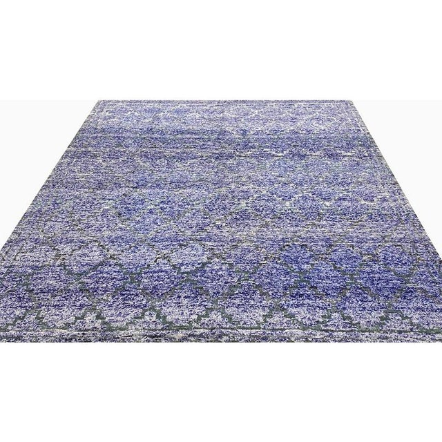 Transitional style area rug featuring an elegant Moroccan trellis design on a purple abrashed background. Hand-woven from...