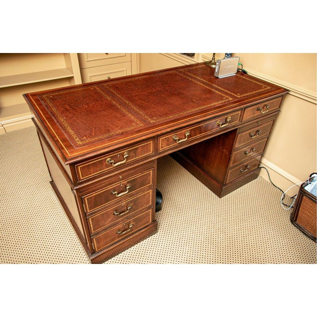 English mahogany pedestal desk with tooled leather top. This Georgian styled desk has raised panels, satinwood inlay, a...