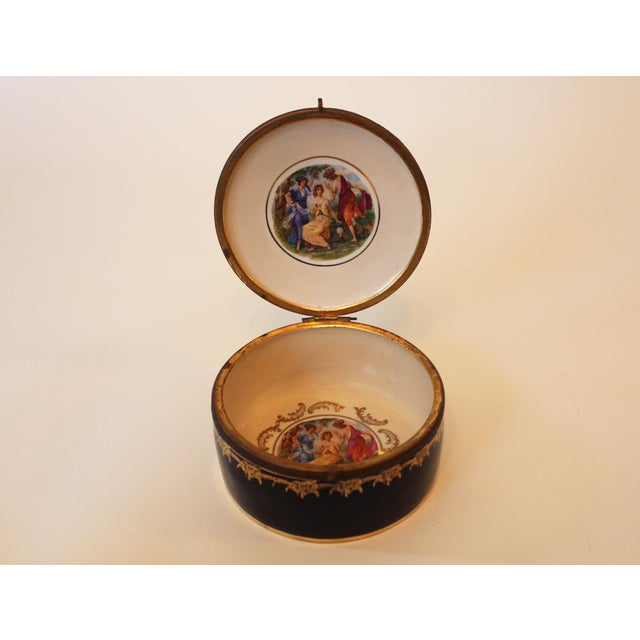 """Porcelain trinket box with lid, marked """"Made in Germany."""" Cobalt blue and gold with a repeated scene of three classical..."""