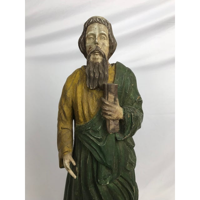 Primitive carved wood, paint and gesso figure of a male saint, carrying a book. In good condition except his right hand...