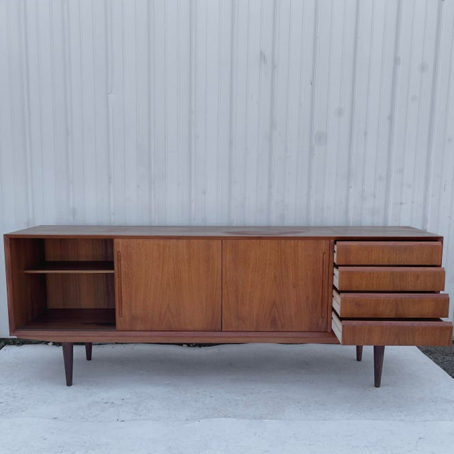 This striking mid-century modern sideboard features stunning Scandinavian Modern design with a mix of drawers and shelved...