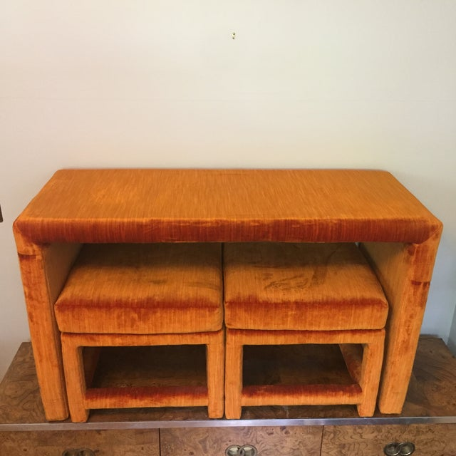 Fabulous console table upholstered in a vibrant orange velvet with glass top. Two matching parsons style ottomans both fit...
