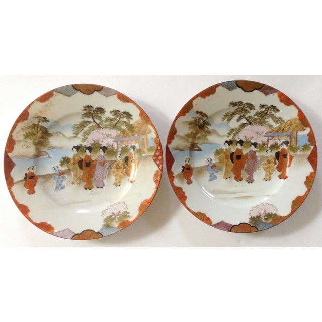 Lovely landscape of women with their children is the motif on this pair of Japanese plates. Both edged in red with gold...