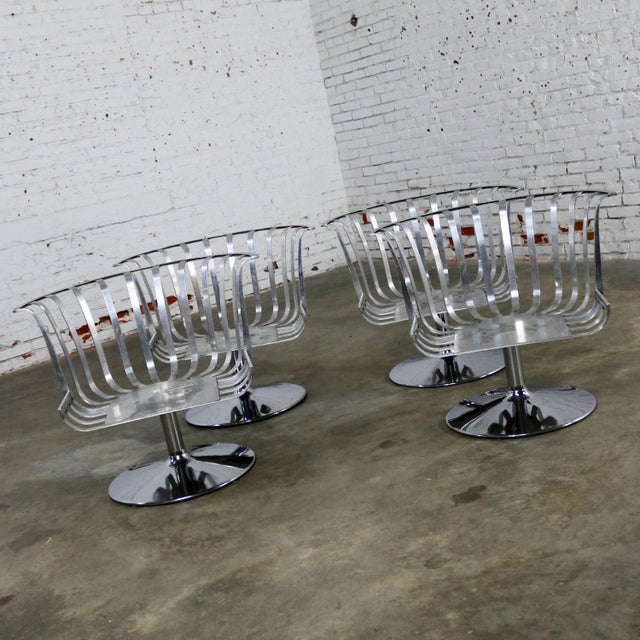Awesome set of four polished aluminum tulip shaped swivel lounge chairs by Russell Woodard. The chairs are in wonderful...