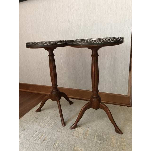 A pair of wood tripod drink tables with brass border on top. Made in the mid 20th century.
