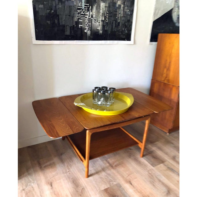 Designed by Peter Hvidt for John Stuart. Solid teak with sculptural features and brass detailing. Each drop leaf is...