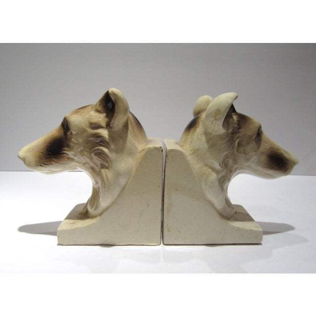 A vintage pair of ceramic dog bust bookends in brown and ivory, circa 1950s. Beautiful patina with overall crazing. Marked...