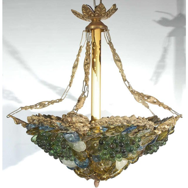 This colorful art glass and brass chandelier is from an earlier part of the last century. The brass frame is supported by...