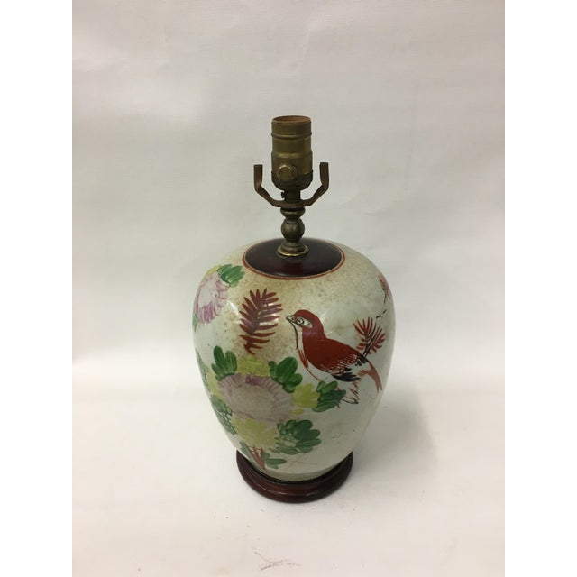 Vintage ceramic ginger jar lamp showcasing traditional motifs; sparrows decorate the jar and are painted with flowers and...