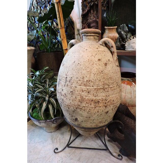 Large Tunisian amphora urn with custom-built iron stand.