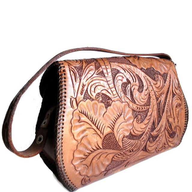 A hand tooled leather purse with flower and leaf design, featuring leather cord stitching around edges. Handbag or...