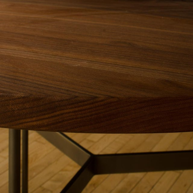 A contemporary Gratz designed occasional table, black walnut top and medium antique bronze finish, 2019.