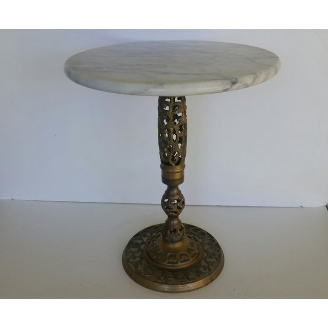 A petite and functional pierced brass table with substantial marble top. In excellent vintage condition, wear is...