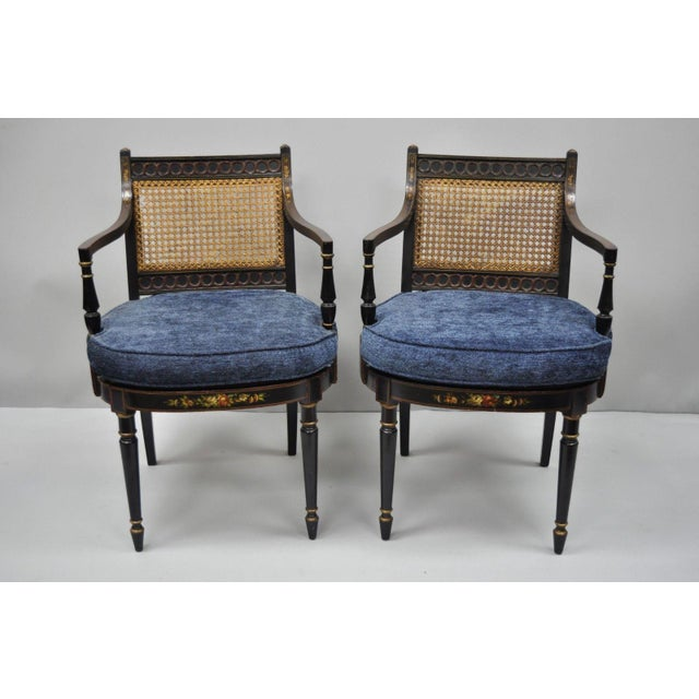 Pair of Antique English Regency Style Black Lacquer Cane Armchairs. Items feature blue loose cushions, cane back and...