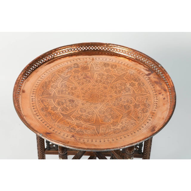 Moroccan antique metal copper tray table with wooden hand-carved Syrian folding base. The hammered metal copper tray is...