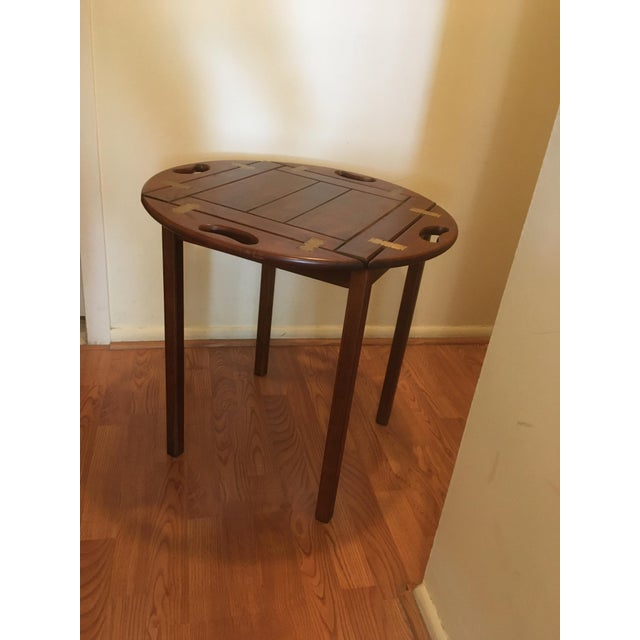 This is a Bombay Company butler table in cherry wood with brass fixtures on the tray.. The sides flip up and can be used...