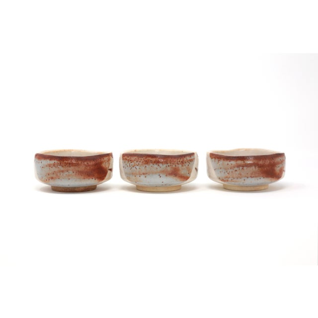 A set of three 1970's Japanese pottery sauce or snack dishes, with unique shape and beautiful hand-painted design.