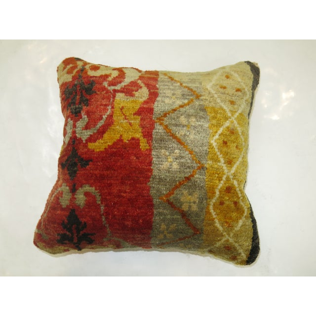 A pillow made from a 19th-century antique oushak rug with red cotton back. Zipper closure and foam insert provided.