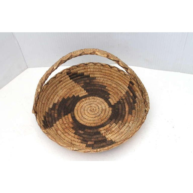 This most unusual Papago Indian basket has a wonderful webbed handle. The base or inset has a whirling log pattern and...