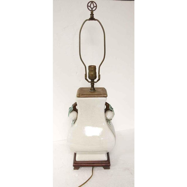 Off white single socket table lamp with a crackled glaze and green and brown leaf details on each side with a wooden base....