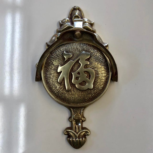 "Brass door knocker with the Chinese symbol for ""welcome"" Minor wear and patina consistent with age. Mounting screws not..."