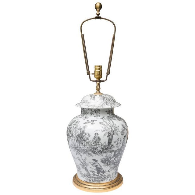 This lidded urn with black and white French Toile motif is situated on a custom giltwood base, circa 20th century.