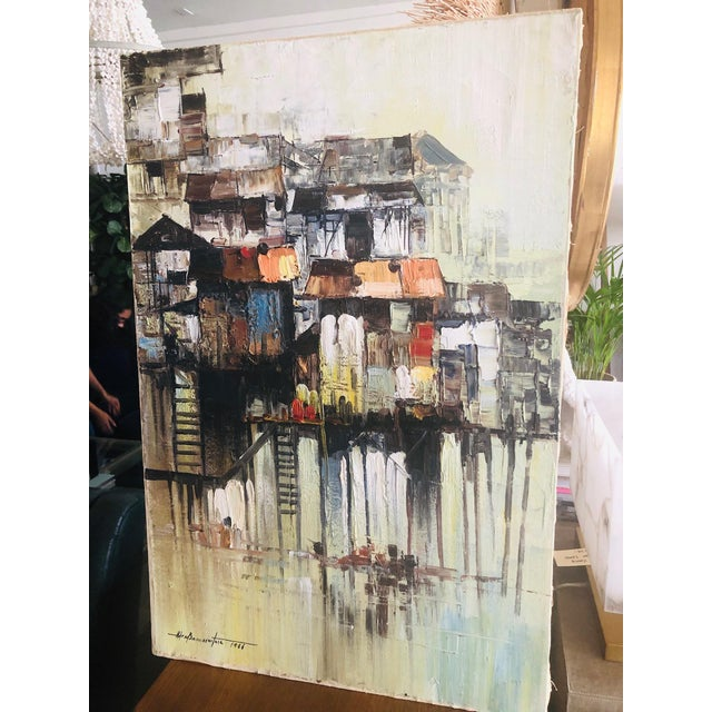 1966 Oil painting of colorful houses on stilts over water. Dominant colors are rusty reds, browns and cream. Artist...