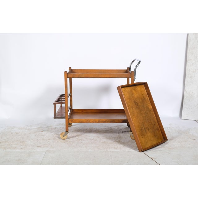 Sleek Mid-Century wooden bar cart. This piece features a removable tray and a hinged drink rack.