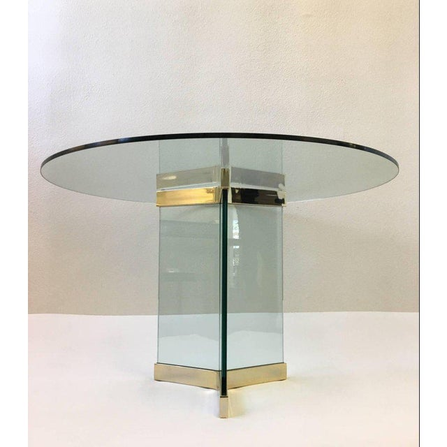 "A polished brass and glass round dining table, designed in the 1970s by Leon Rosen for Pace collection. Measures: New 48""..."
