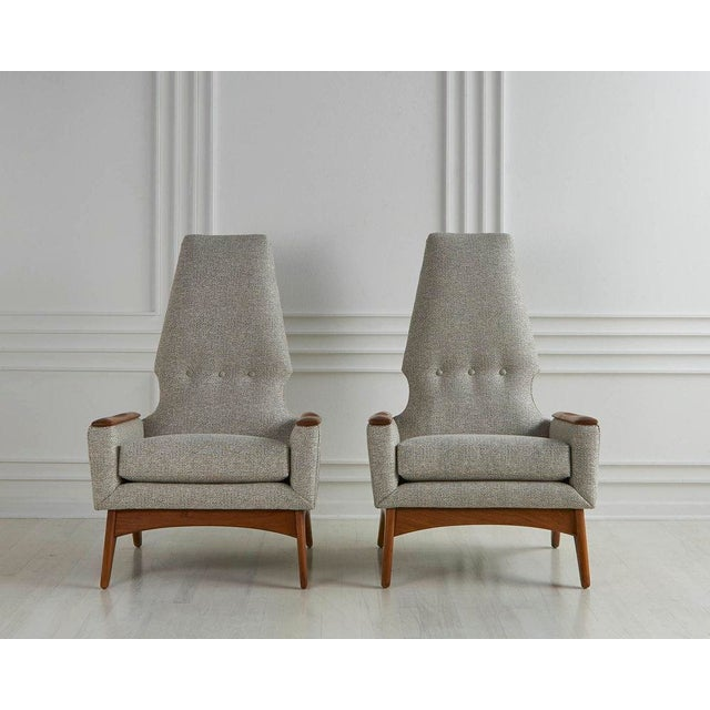 A sculptural pair of 1960's lounge chairs featuring a teak wood frame and a a geometric high back. The chairs have been...