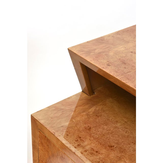 The square top above a canted cut-out above two drawers on brass feet.