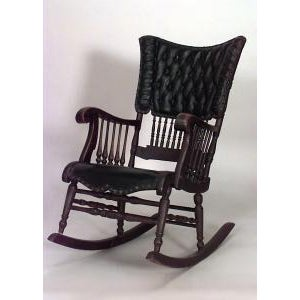 American Victorian oak and black tufted leather rocking chair with spindle design