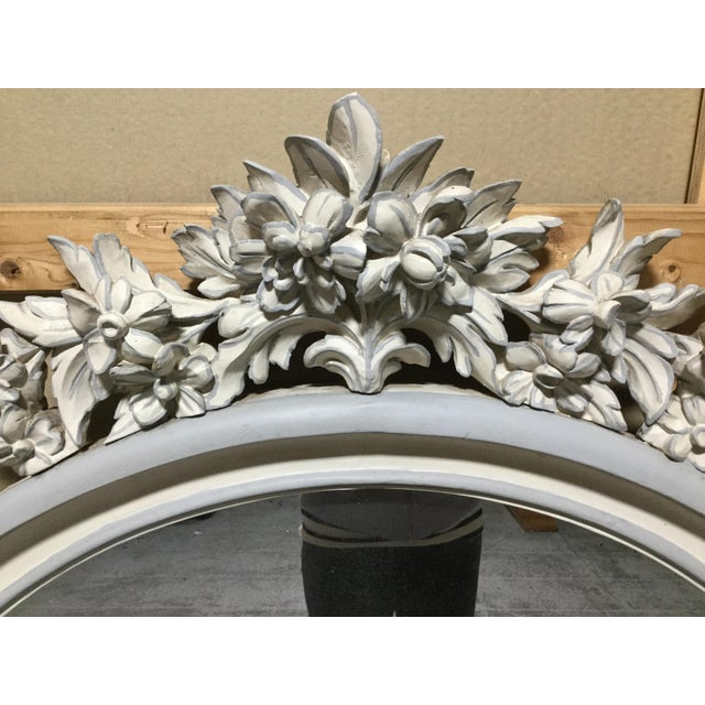 Elegant French Painted Mirror features a fabulous array of carved flowers at the top. Painted in antique white and soft...