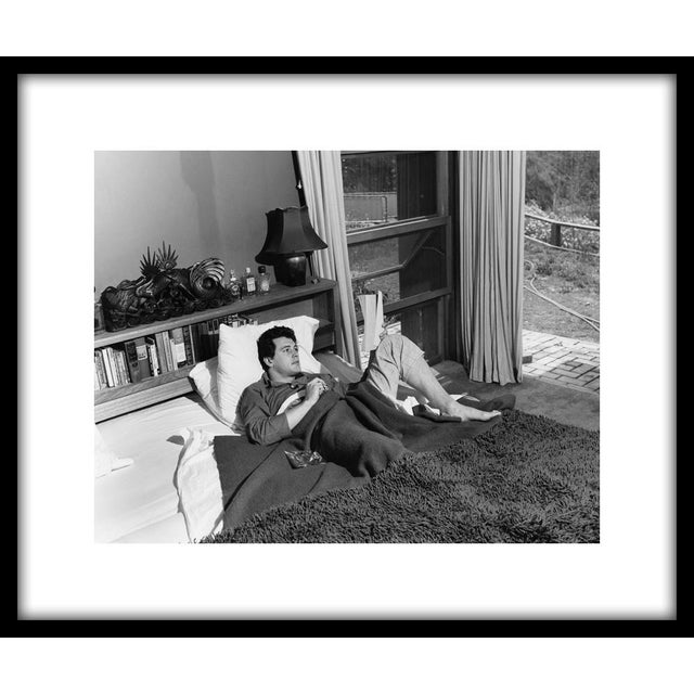 """Rock Hudson at his North Hollywood home, 1952. 11"""" x 14"""" silver gelatin fiber based print signed on verso by the..."""