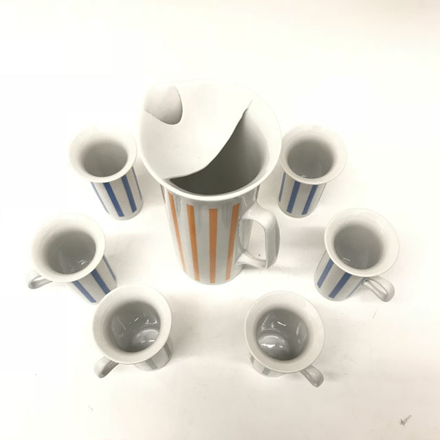"7 price Porcelain drinkware set with pitcher and six cups, designed by Lagardo Tackett. Pitcher 5"" d X 10"" h Cups 2.75"" d..."