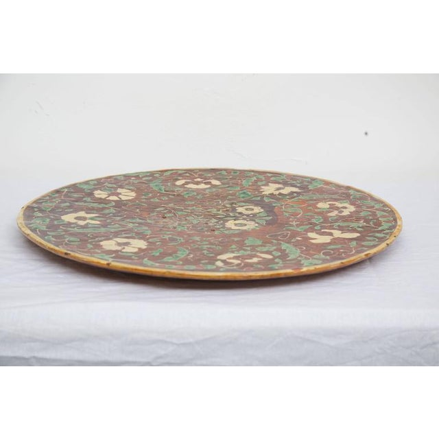 This wonderful painted and glazed Italian charger offers an array of earth tones with a mud red and rust background and...