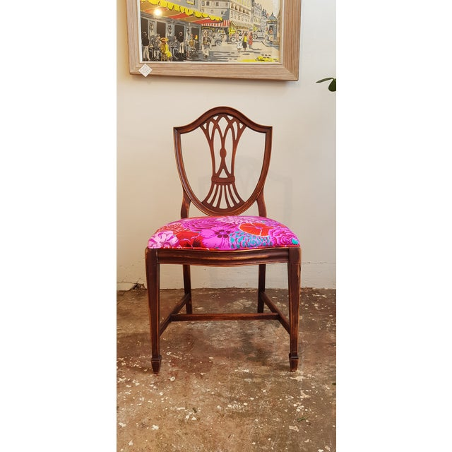 Unique and bold dining chair set with a mix of vibrant print fabric by Kaffe. Chairs are made with a solid wood frame,...