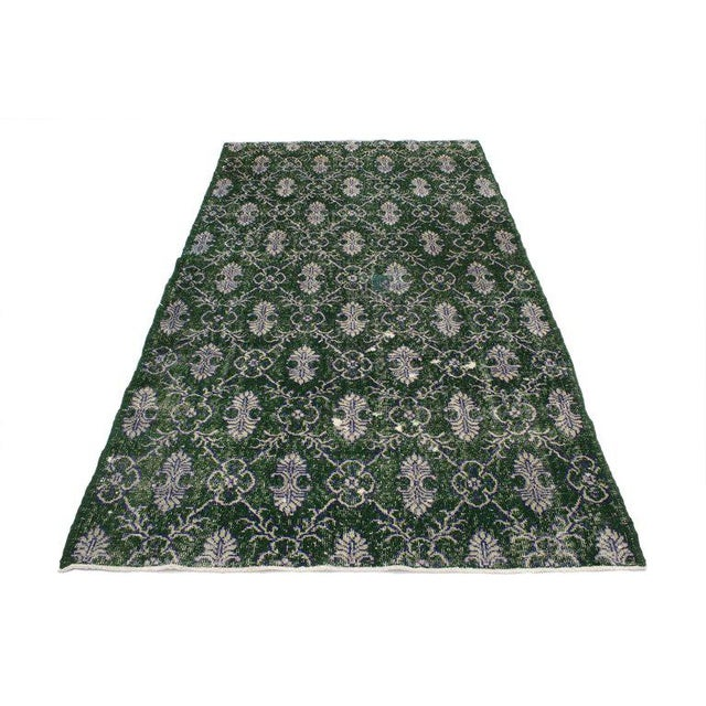 This hand-knotted wool dark green distressed Turkish Sivas rug features a cusped lozenge garden trellis pattern composed...