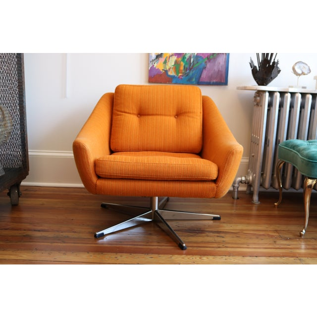 This super fun chair sits low and swivels. Original orange tweed fabric is in pretty good shape - just a tiny bit of...