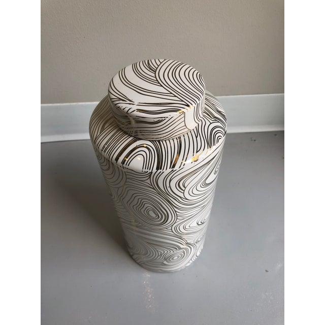 Large Tozai Home ceramic gold geometric covered circular tunnel design tea jar.