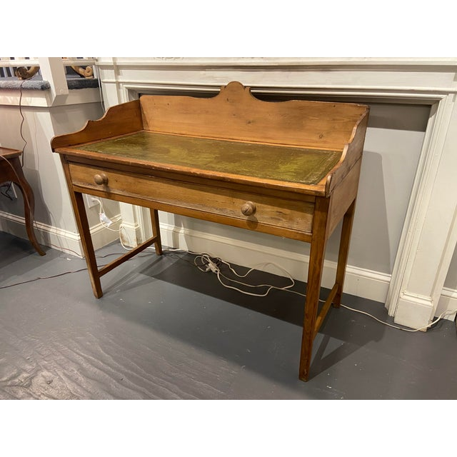 This desk is a beautiful antique piece. It is made of knotty pine. There is a green tooled leather desktop with gold...