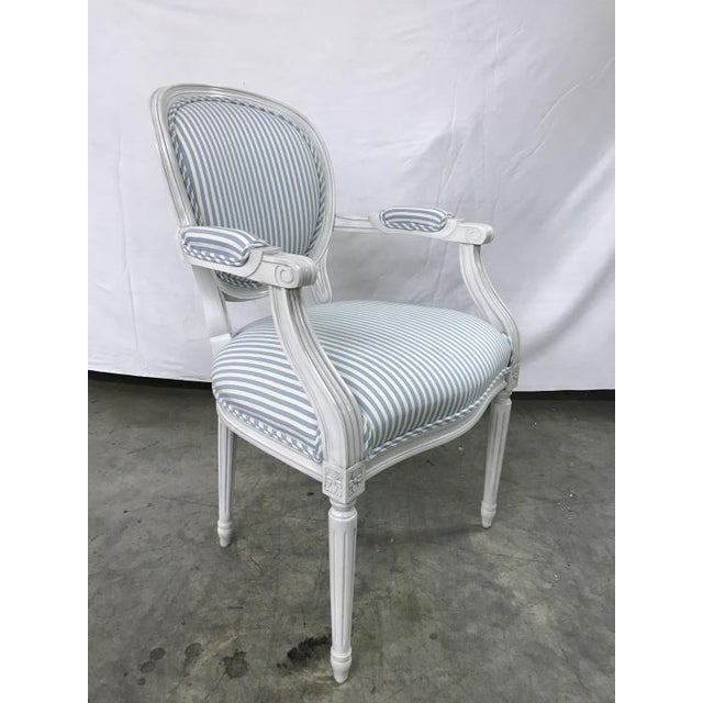 The Anne Arm Chair is a first quality market sample that features a Baby Blue Fabric with an Oyster Finish.