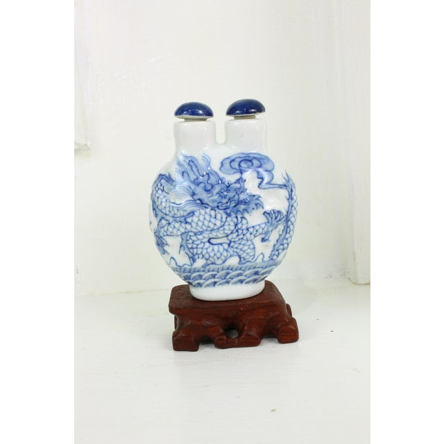 Up for sale is this Asian blue & white double head, porcelain snuff bottle on a stand.