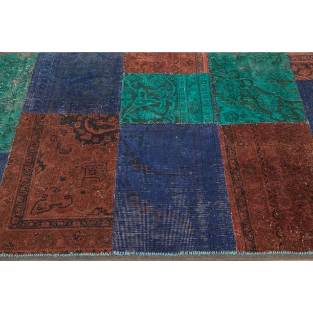 A patchwork carpet made with vintage rugs with all over floral designs in a deep blue, teal, and brown. Overdyed and...