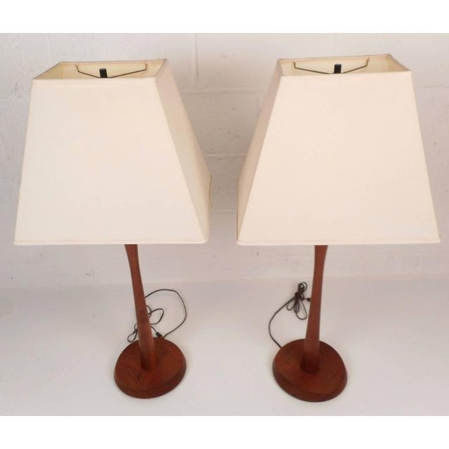 Elegant pair of vintage modern lamps feature unique sculpted bases complimented by bright white shades. They are made of...