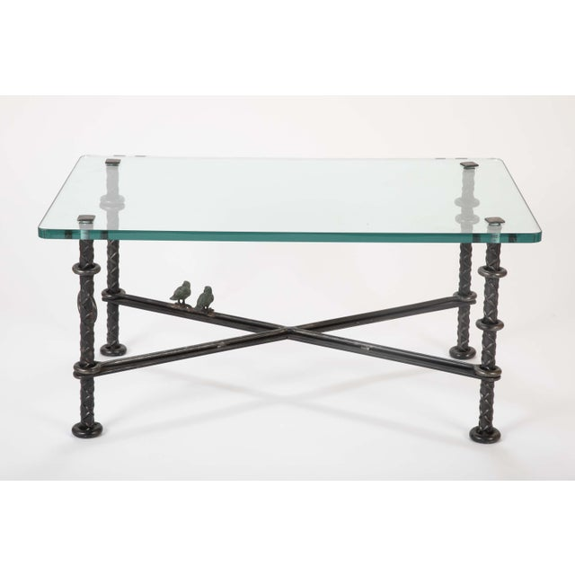 A magnificent patinated wrought iron coffee table by Llana Goor having two figurative sculpted birds. Signed on leg. Late...
