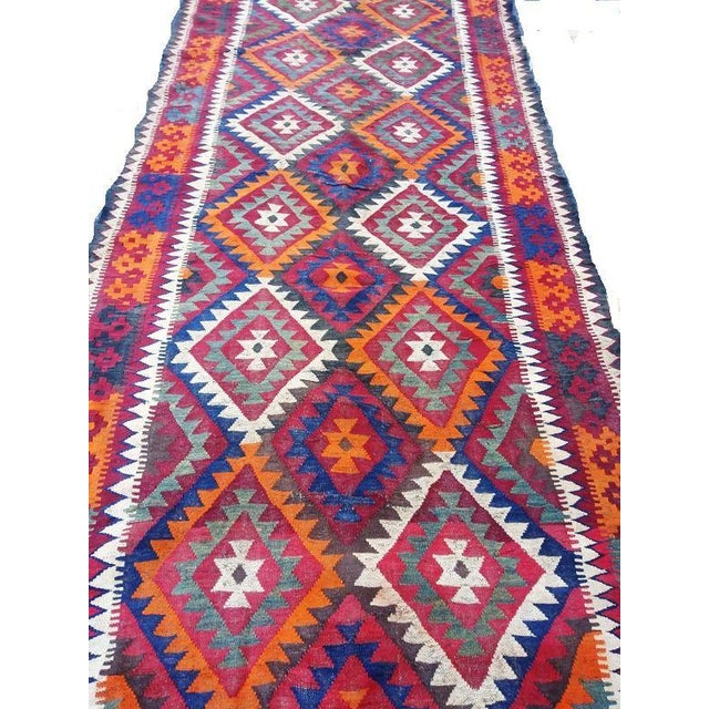 This is a vintage caucasian Kilim rug that was handwoven from wool. The flatweave design features geometric medallions....