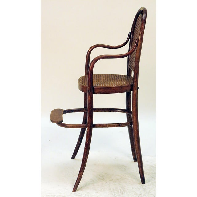 Bent wood child's high chair having a step with caned back and seat. In the manner of Thonet, circa 1900. Decorative use...